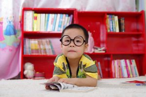 adorable boy with blur bookcase background